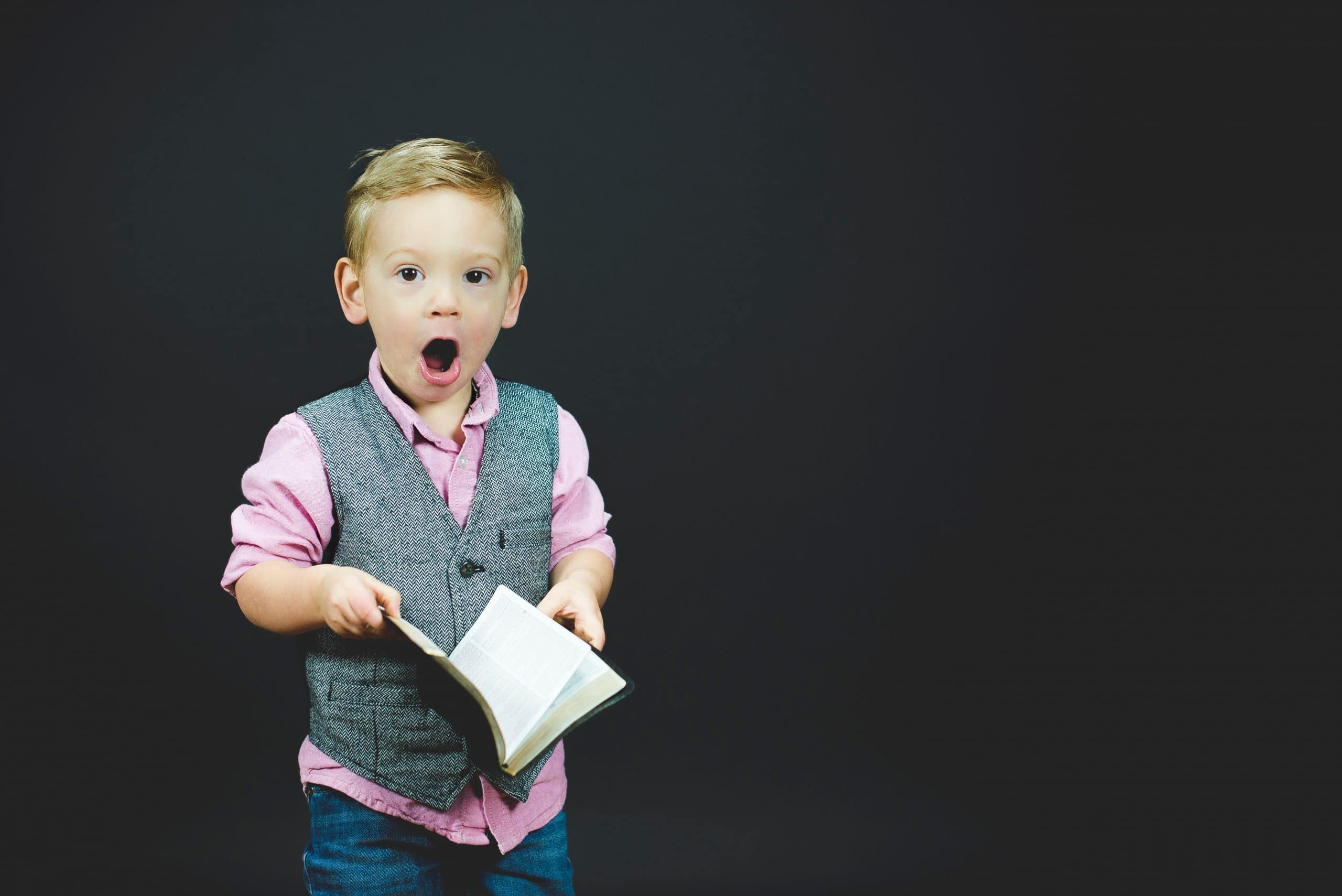 Shocked child holding Bible - photo by Ben White